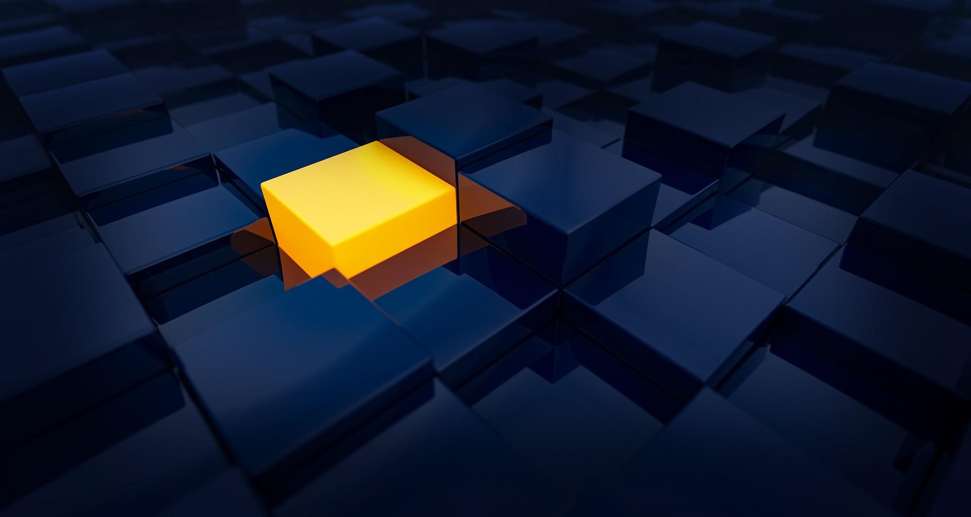 Una scatola gialla che emerge rispetto alle altre attorno di colore scuro in penombra